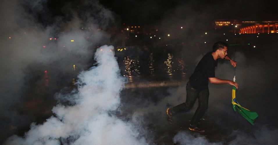 20.jun.2013 - Manifestantes fogem de bombas de gás lacrimogêneo disparadas pela polícia durante protesto em frente a sede do Ministério das Relações Exteriores, em Brasília