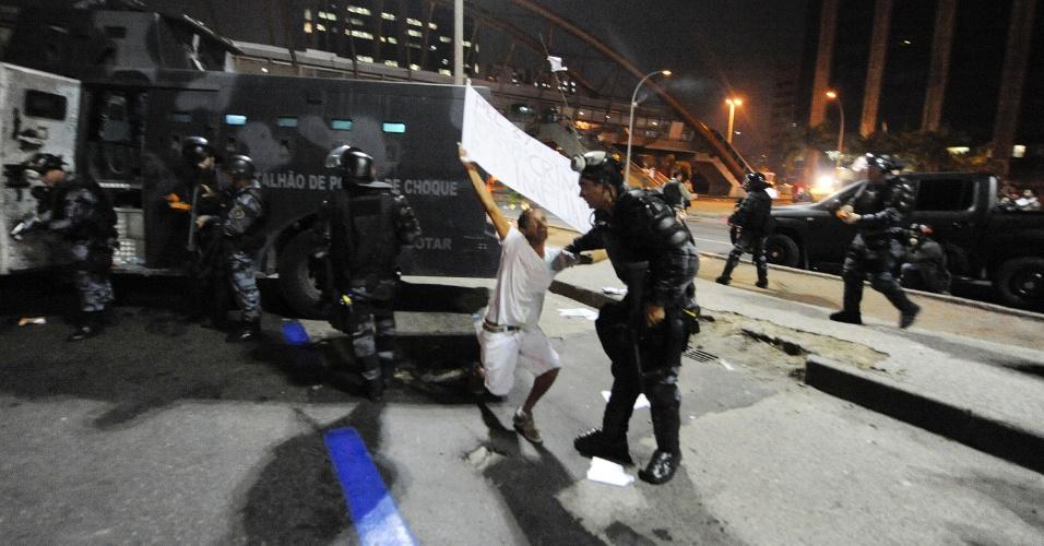 20.jun.2013 - Policiais retiram manifestante que estava ajoelhado em via do centro do Rio de Janeiro em mais uma noite de protesto