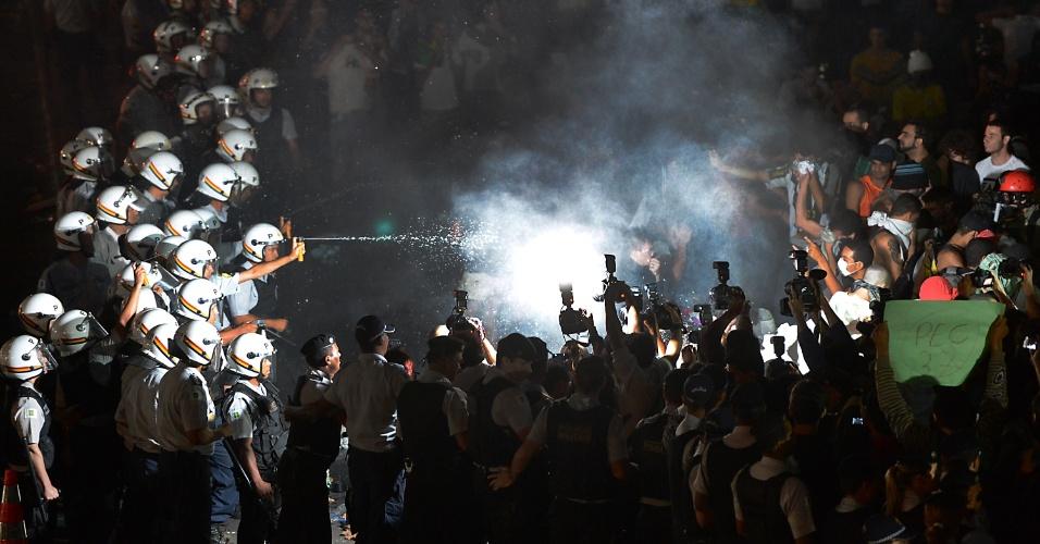 20.jun.2013 - Policial joga spray de pimenta em manifestantes durante mais uma noite de protesto na Esplanada dos Ministérios, em Brasília