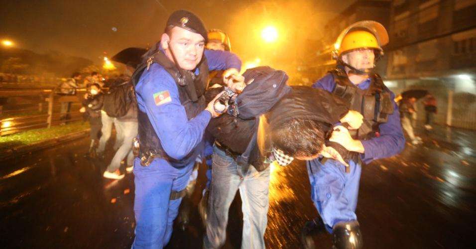 20.jun.2013 - Cerca de 30 mil manifestantes marcharam pelas ruas do centro de Porto Alegre na noite desta quinta-feira. Novamente, o protesto teve depredação e confronto entre policiais e manifestantes. Na foto, jovem é detido pelos policiais