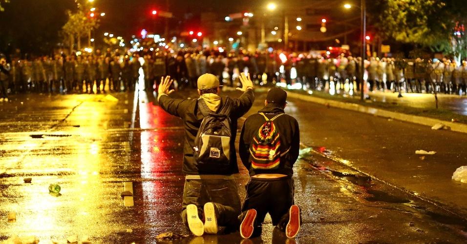 20.jun.2013 - Cerca de 30 mil manifestantes marcharam pelas ruas do centro de Porto Alegre na noite desta quinta-feira. Novamente, o protesto teve depredação e confronto entre policiais e manifestantes. Na foto, três pessoas ajoelham diante do batalhão de choque da Brigada Militar