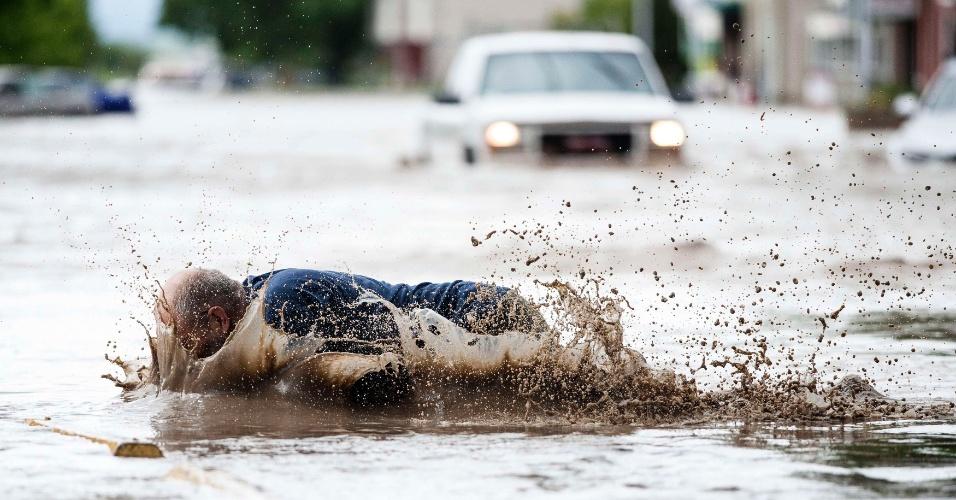 20.jun.2013 - Homem tropeça e cai em rua alagada após checar a situação de sua loja, no centro de High River, no oeste do Canadá. O homem, chamado François Gougeon, ficou molhado, mas não se machucou. Foi declarado estado de emergência em High River, com a evacuação dos moradores