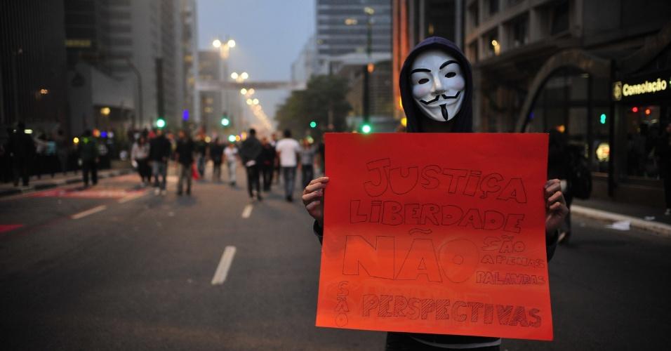 20.jun.2013 - Manifestante mascarado carrega cartaz da avenida Paulista, na região central de São Paulo (SP), em protesto nesta quinta-feira, mantido mesmo após a redução das passagens de ônibus, metrô e trem na capital paulista, anunciada ontem