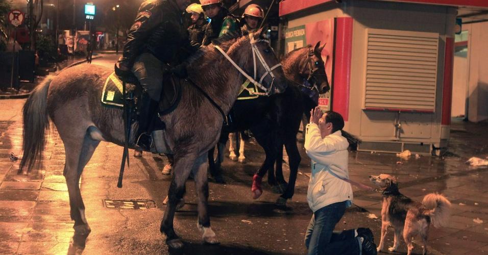20.jun.2013 - Mulher se ajoelha na frente de policiais da tropa de choque durante varredura da cavalaria, em Porto Alegre, Rio Grande do Sul