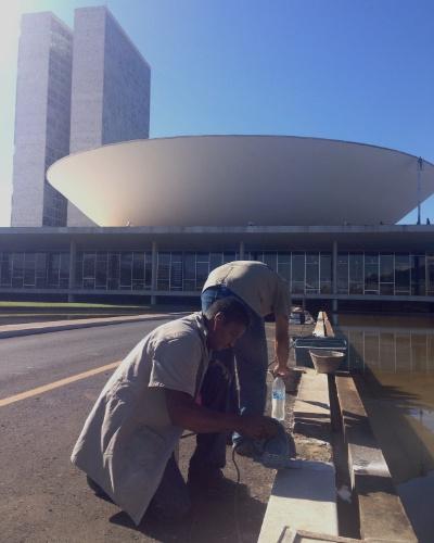 21.jun.2013 - Funcionários consertam e pintam sarjeta próxima ao espelho d'água do Congresso Nacional, em Brasília. A área foi depredada por manifestantes na noite de quinta-feira (21), dia de maior mobilização nacional - cerca de 1 milhão de pessoas foram às ruas no país