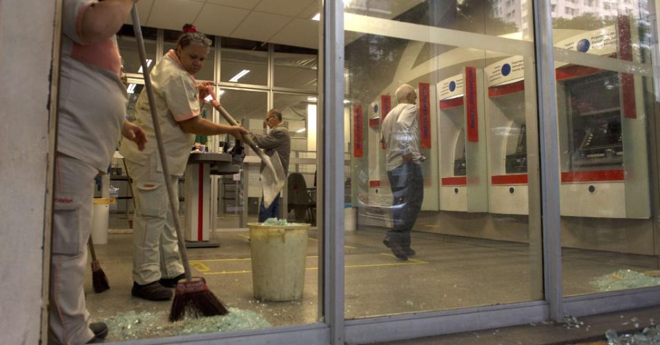 21.jun.2013 - Mulheres fazem limpeza em agência bancária depredada em protesto na avenida Presidente Vargas, centro do Rio de Janeiro