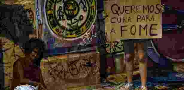 Manifestante segura cartaz perto de sem-teto no centro de Recife (PE) - Yasuyoshi Chiba/AFP