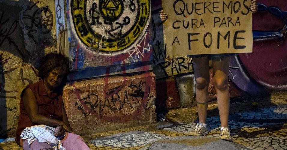 20.jun.2013 - Manifestante segura cartaz perto de sem-teto no centro de Recife (PE). Mais de um milhão de pessoas saíram às ruas no Brasil para protestar na última quinta