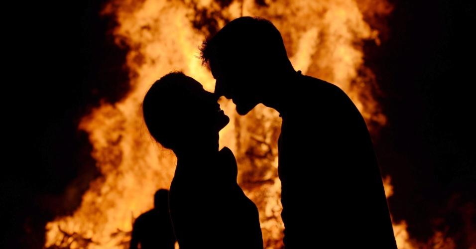 21.jun.2013 - Casal se beija diante de fogueira feita em festival em celebração do solstício de verão no hemisfério norte, em Freiberg (Alemanha), nesta sexta-feira (21)
