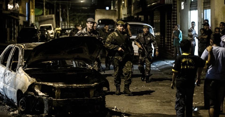 21.jun.2013 - Policiais guardam entrada da favela do Jardim Andaraí, zona norte de São Paulo, onde um PM foi baleado em confronto com manifestantes que protestavam na rodovia Presidente Dutra. Um carro foi atingido por tiros, e outro foi incendiado pelos manifestantes. A polícia não soube informar o estado de saúde do PM e nem quantas pessoas ficaram feridas no confronto