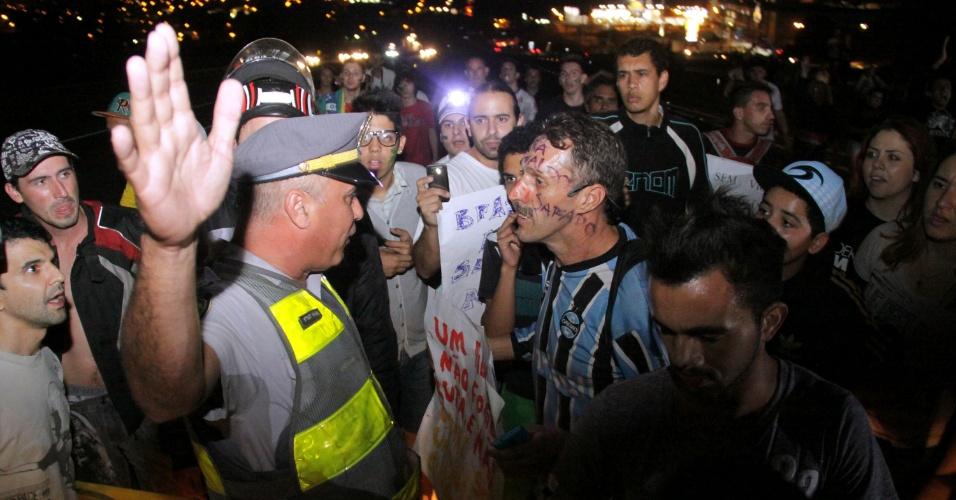 22.jan.2013 - Policial e manifestante discutem durante protesto que interditou o km 99 da rodovia Raposo Tavares em Votorantim (105 km de São Paulo), nesta sexta-feira (21). Os manifestantes entoaram gritos contra a corrupção e outras causas