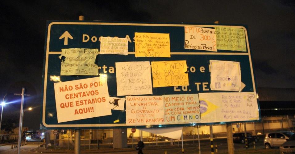 22.jun.2013 - Cartazes de protesto são colados em placa de sinalização de rampa de acesso ao embarque do aeroporto Internacional de Guarulhos, na madrugada deste sábado (22)