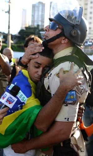 22.jun.2013 - Manifestante abraça policial durante ato em Salvador, na tarde deste sábado. Durante a noite, houve confronto e policiais militares jogaram bombas de gás lacrimogêneo contra um grupo menor de manifestantes