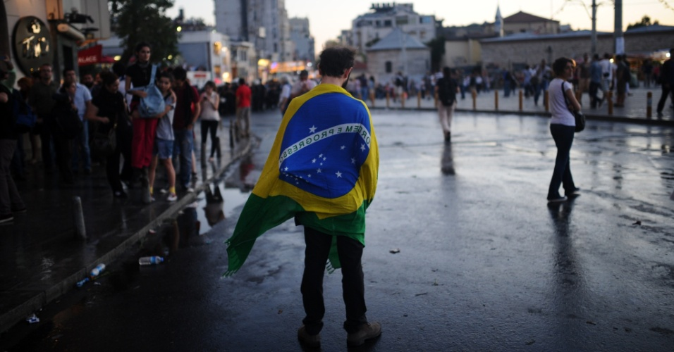22.jun.2013 - Manifestante com a bandeira do Brasil nas costas é visto na praça Taksim, em Istambul (Turquia). Uma nova onda de protestos ocorreu neste sábado e a polícia usou canhões de água para dispersar os ativistas