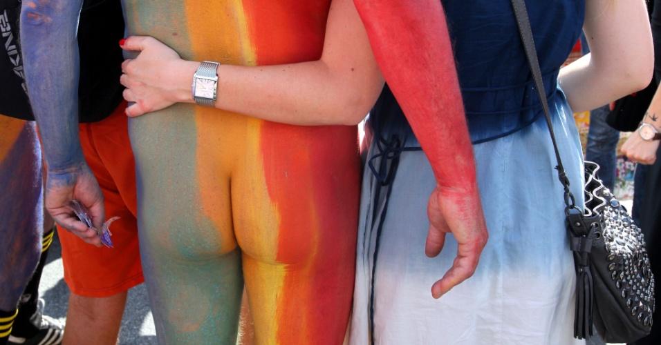 22.jun.2013 - Mulher abraça homem nu pintado com as cores do arco-íris durante a Parada da Christopher Street, em Berlim (Alemanha), que pede direitos iguais para casais homossexuais