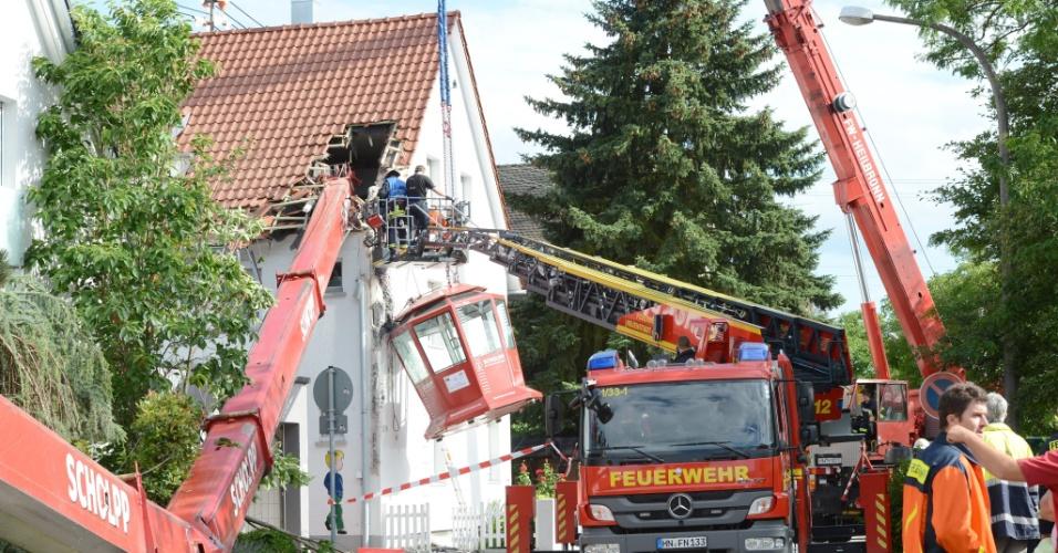 22.jun.2013 - Policiais, bombeiros e equipes de resgate se reúnem após um guindaste que carregava uma cabine panorâmica cair sobre o telhado de uma casa deixando pelo menos 14 pessoas, que estavam dentro da cabine, feridas, em Neuenstadt am Kocher, na Alemanha, neste sábado (22). O acidente aconteceu durante uma festa organizada por uma escola local