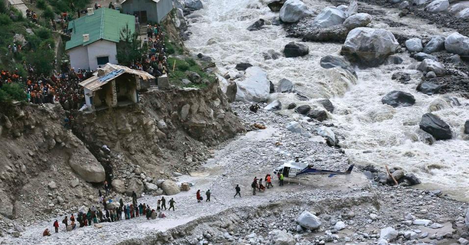 22.jun.2013 - Soldados ajudam pessoas a embarcarem em helicóptero durante operação de evacuação na cidade de Govindghat, na região indiana do Himalaia. As primeiras chuvas de monção transbordaram o Ganges, rio mais longo da Índia, e causaram deslizamentos de terra que já causaram a morte de mais de 500 pessoas