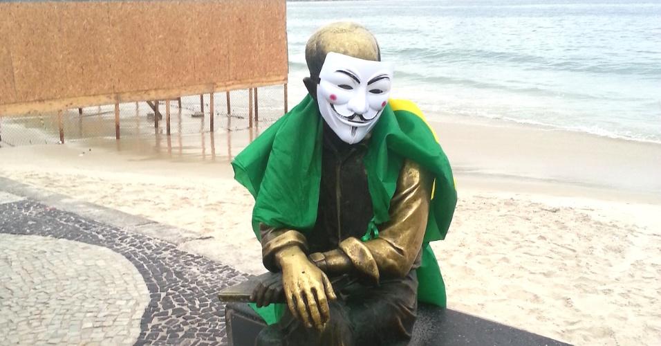 Estátua de Carlos Drummond de Andrade, na orla de Copacabana, no Rio de Janeiro, foi adornada por manifestantes com a bandeira do Brasil e com máscara que vem sendo usada em diversos protestos por todo o país