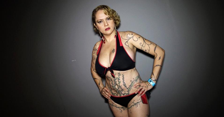Mulher posa para foto durante exibição anual de tatuagens conhecida como