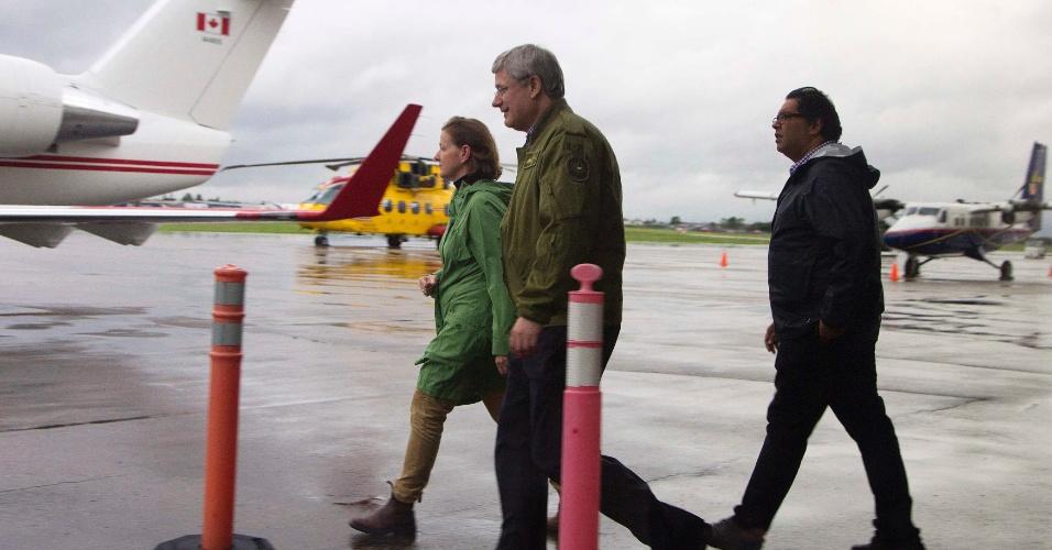 21.jun.2013 - O primeiro-ministro do Canadá Stephen Harper (centro), a governadora do Estado de Alberta, Alison Redford (esquerda) e o prefeito de Calgary, Naheed Nenshi, caminham para helicóptero para visitar áreas atingidas por inundações em Calgary. Milhares de pessoas foram evacuadas de suas casas por causa das inundações que atingem o país