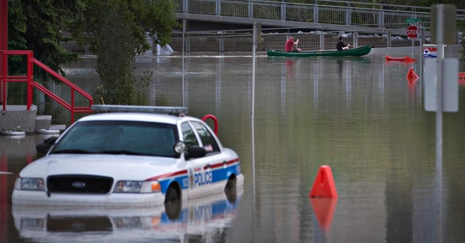 21.jun.2013 - Pessoas andam de canoa próximo a carro de polícia submerso em rua alagada de Calgary, no Estado de Alberta, no Canadá. Três pessoas morreram por causa das enchentes e milhares de moradores foram obrigados a deixar suas casas
