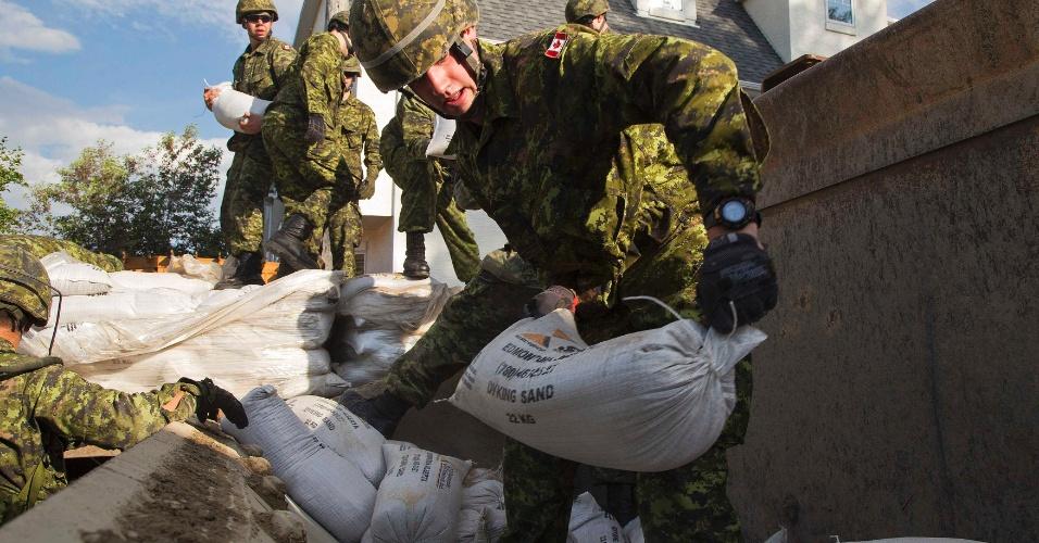 22.jun.2013 - Militares canadenses carregam sacos de areia para conter inundação em bairro de Calgary, no Canadá, no Estado de Alberta. A enchente obrigou milhares de moradores a deixarem suas casas