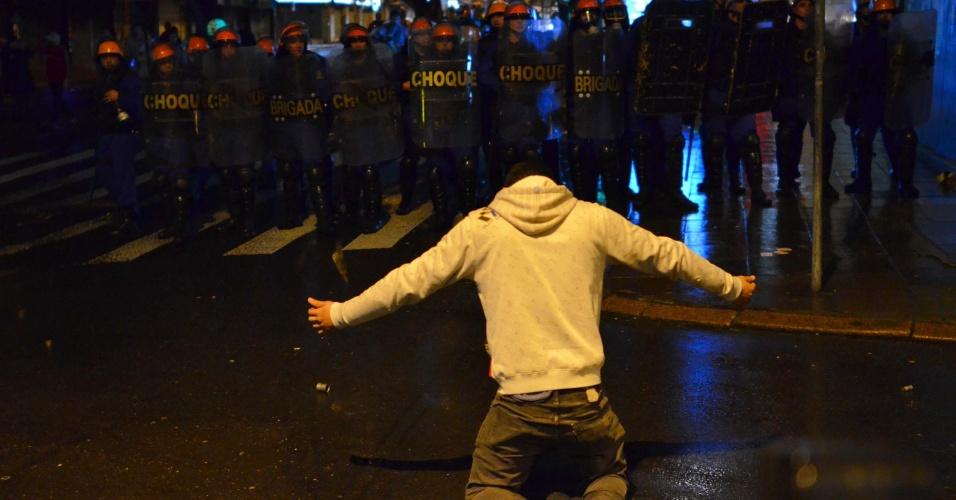 24.jun.2013 - Manifestante se posiciona em frente à tropa de choque, durante confronto com a Brigada Militar em noite de protesto em Porto Alegre