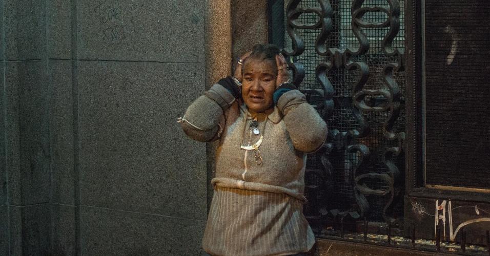 24.jun.2013 - Mulher tapa os ouvidos durante confrontos entre policiais e manifestantes protesto em Porto Alegre, na noite desta segunda-feira (24). Cerca de 10 mil pessoas se reuniram nas ruas da cidade
