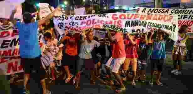 Crianças moradoras da comunidade da Rocinha, no Rio, carregam faixa durante manifestação no bairro - Chistophe Simon/AFP Photo