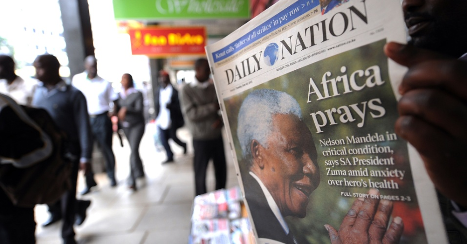 """25.jun.2013 - Homem lê jornal cuja capa destaca que a """"África ora por Mandela"""", em Nairobi, no Quênia. Aos 94 anos, o ex-presidente da África do Sul e nobel da paz Nelson Mandela está internado em estado crítico em um hospital de Pretória, desde 8 de junho"""