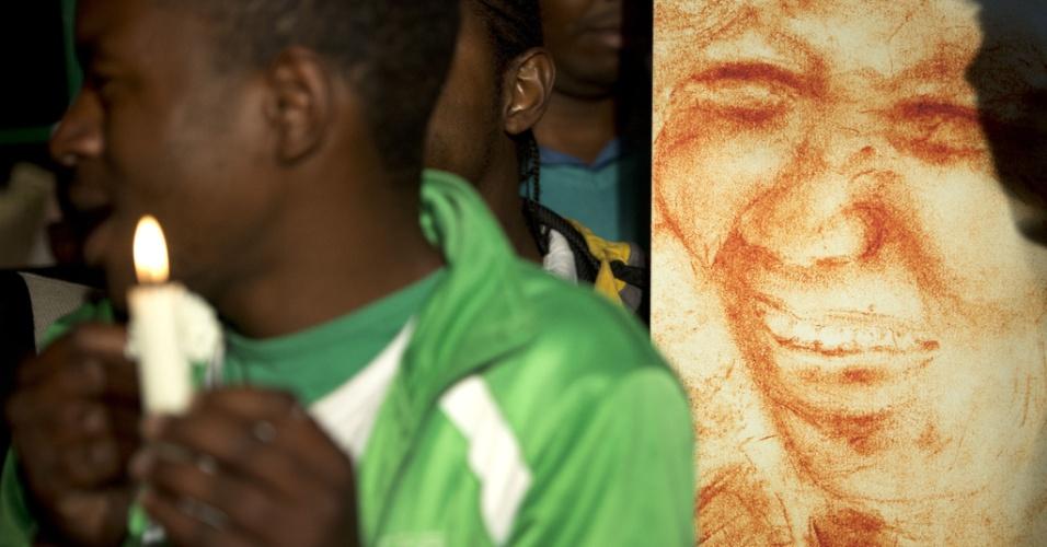 25.jun.2013 - Jovem segura vela durante uma vigília do lado de fora do Hospital do Coração Mediclinic em Pretória, onde o ex-presidente da África do Sul Nelson Mandela está internado em estado crítico. O grupo orou e cantou canções religiosas em apoio a Mandela