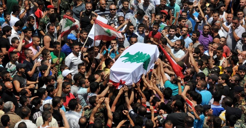 25.jun.2013 - Libaneses carregam caixão do soldado Taleb Hassan Mama em funeral realizado no distrito de Jabal Mohsen, no norte da cidade de Trípoli. Ele foi morto durante confronto com radicais sunitas no sul do Líbano
