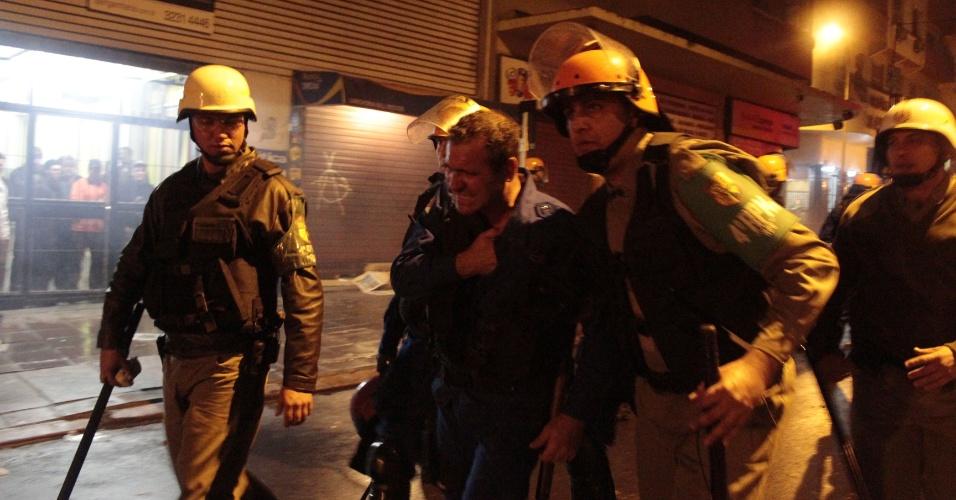 25.jun.2013 - Policial é ferido em confronto com manifestantes que atiravam pedras e rojões contra a polícia na avenida Borges de Medeiros, uma das principais do centro de Porto Alegre, na noite de segunda-feira (24)