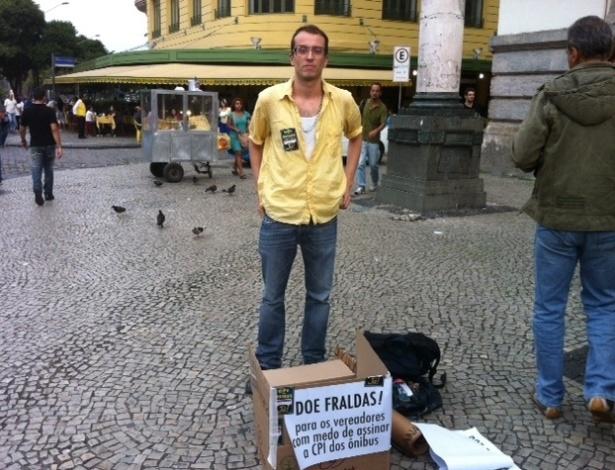 """25.jun.2013 - Um ativista encontrou uma forma inusitada e criativa de protestar na frente da Câmara Municipal do Rio de Janeiro. O artista """"Rafucko"""" trouxe uma caixa para receber fraldas para os """"vereadores com medo de assinar a CPI dos ônibus"""". Ele mesmo trouxe uma e recebeu outras duas. Dos 51 vereadores que compõem a casa, 27 assinaram o requerimento e 24 não"""