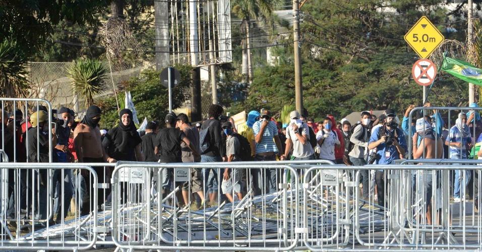 26.jun.2013 - Homens derrubaram grades de contenção na avenida Antônio Carlos, em Belo Horizonte, nas proximidades do Estádio do Mineirão, montadas pela Polícia Militar, durante protesto
