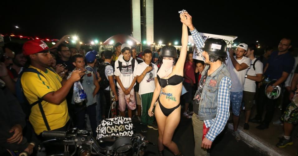 26.jun.2013 - Manifestante aparece de biquíni no meio da manifestação e vira atração em frente ao Congresso Nacional, em Brasília