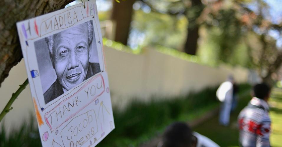 27.jan.2013 - Cartaz em apoio a Nelson Mandela é pendurado em árvore do jardim em frente à casa do ex-presidente da África do Sul, em Houghton, subúrbio de Johanesburgo