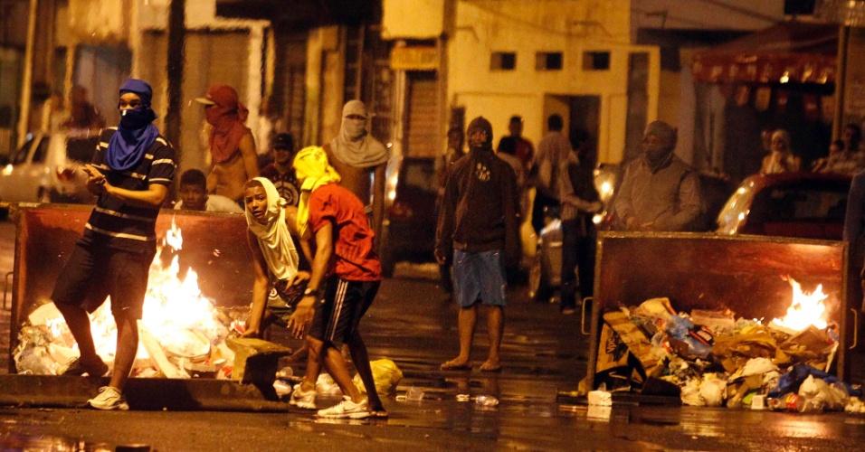 27.jun.2013 - Manifestantes ateam fogo em contêineres em Salvador, na noite desta quinta-feira (27). O grupo bloqueou vias de acesso à estação da Lapa e entraram em confronto com a polícia militar, que reagiu com balas de borracha e gás lacrimogêneo. Treze pessoas foram detidas suspeitas de depredarem ônibus e atirarem pedras e fogos de artifícios contra os PMs