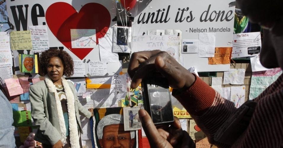27.jun.2013 - Mulher tira fotos em frente ao muro com mensagens em apoio a Nelson Mandela, que está internado desde o dia 8 de junho em um hospital de Pretoria, na África do Sulo