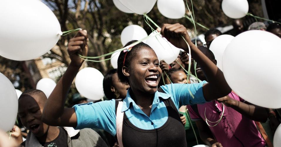 27.jun.2013 - Pessoas dançam com balões brancos em solidariedade ao estado crítico de Nelson Mandela na frente do hospital onde ele está internado desde o dia 8 de junho, em Pretoria