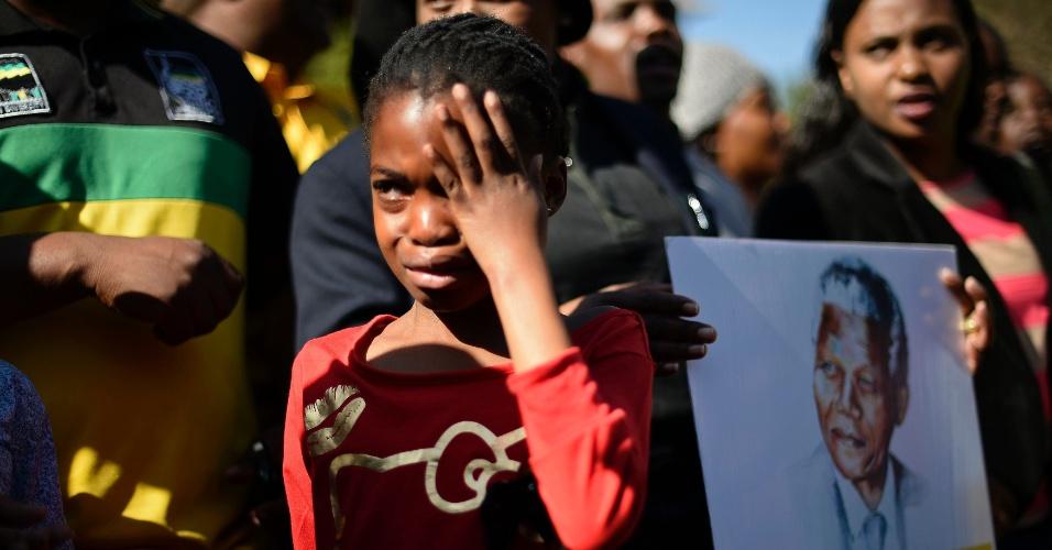 28.jun.2013 - Garota chora em frente ao Hospital do Coração Mediclinic, em Pretória, na África do Sul, nesta sexta-feira (28), onde o ex-presidente sul-africano Nelson Mandela está internado em estado crítico