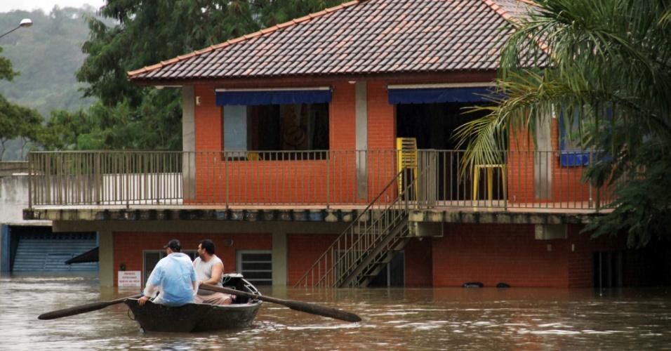 Moradores andam de barco em rua alagada de Foz do Iguaçu (PR), após chuvas intensas que inundaram diversas cidades paranaenses. O governador, Beto Richa, assinou na manhã desta sexta-feira (28), em Maringá, um decreto que estabelece situação de emergência em 59 municípios paranaenses mais atingidos pelas chuvas