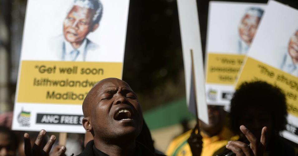 28.jun.2013 - Homem canta do lado de fora do hospital onde o ex-presidente da África do Sul Nelson Mandela está internado, em Pretória, nesta sexta-feira (28)