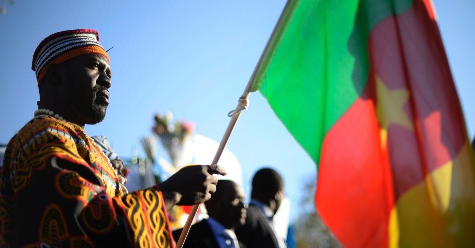 28.jun.2013 - Homem carrega a bandeira de Camarões durante vigília por Nelson Mandela, diante do hospital Medi-Clinic, em Pretoria (África do Sul), onde o ex-presidente está internado desde o dia 8 de junho. Segundo o presidente Jacob Zuma, Mandela está melhor hoje do que na noite passada, apesar de seguir em estado crítico