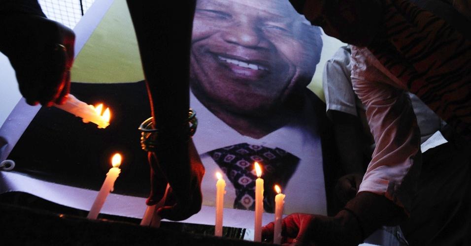 28.jun.2013 - Membros e simpatizantes da ONG Associação de Nelson Mandela, em Bangalore, na Índia, acendem velas diante da imagem do ex-presidente sul-africano, que está internado devido a uma infecção pulmonar
