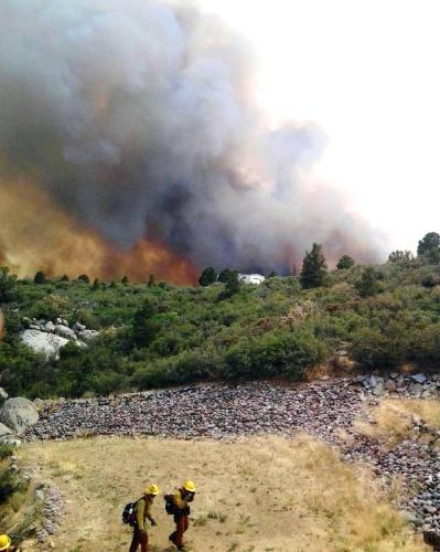 1º.jul.2013 - Incêndio devasta mata da cidade de Yarnell, no Arizona (EUA), enquanto bombeiros se afastam do local na tarde do último domingo (30)