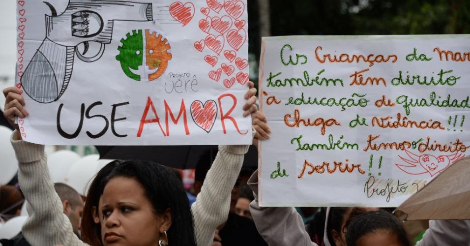 2.jul.2013 - Manifestantes exibem cartazes contra violência, em protesto no Complexo da Maré, Rio de Janeiro