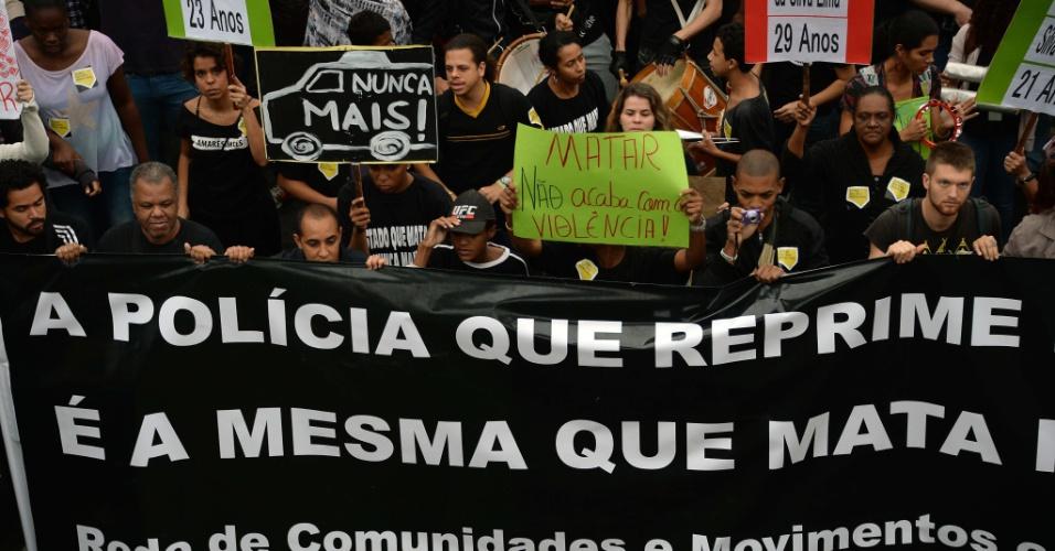 """2.jul.2013 - Manifestantes exibem faixa : """"A polícia que reprime é a mesma que mata"""", durante protesto pelo fim dos massacres no Complexo da Maré, Rio de Janeiro"""