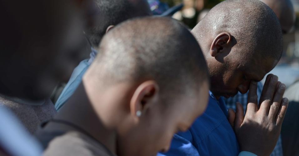 2.jul.2013 - Pessoas oram do lado de fora do hospital do coração Mediclinic, onde o ex-presidente da África do Sul Nelson Mandela está internado, em Pretória, na África do Sul, nesta terça-feira (2).. Mandela, que completará 95 anos em 18 de julho, está em estado crítico, mas estável
