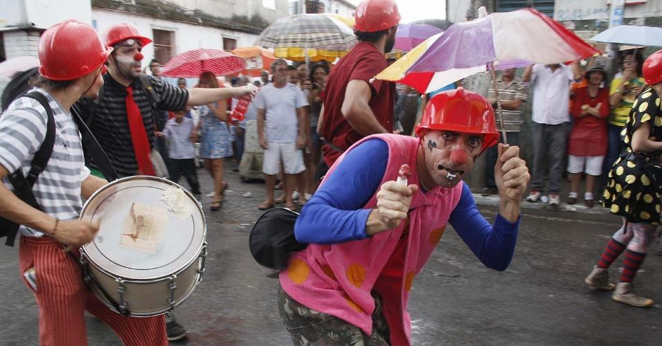 2.jul.2013 - Vestido de palhaço, homem aponta uma arma de brinquedo em alusão à repressão policial que marcou grandes atos pelo Brasil, no último mês. Manifestantes protestaram durante o cortejo do Dois de Julho, que marca a independência da Bahia, pelo bairro da Lapinha, em Salvador
